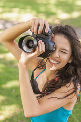 High angle view of cheerful young woman taking a picture