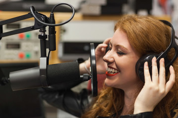 Cheerful beautiful singer recording a song