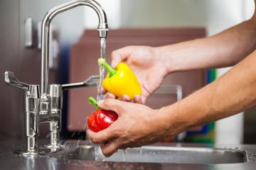 Kitchen porter washing pepper under running tap