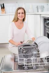 Cheerful gorgeous model kneeling behind dish washer
