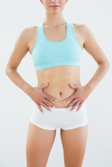Mid section of a fit woman in sportswear with hands on belly