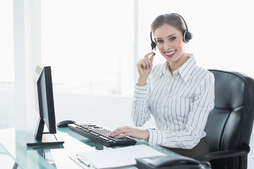 Gorgeous chic agent wearing headset sitting at her desk