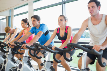 Determined people working out at spinning class