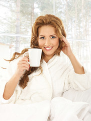 A young and attractive woman drinking coffee in a towel