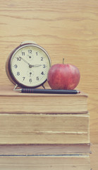Vintage clock and apple with pancil on old books