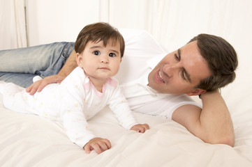 Father and Baby Girl playing on bed