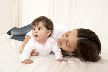 Mother and daughter playing on bed isolated