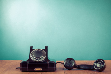 Retro black telephone on table in front mint green background