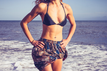 Young woman with toned abs standing on the beach