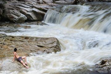A Man enjoying the beauty of waterfall