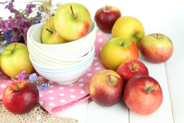Juicy apples on plate on white wooden table