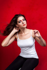 Girl with flying hair on red background