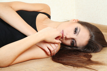 Lonely sad woman lying on floor near wall