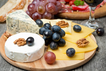 Assorted cheese, grapes, wine and sausages