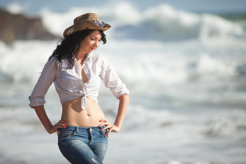 Fashion woman with cowboy hat on the beach