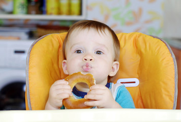 funny baby boy eating round cracknel