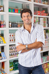 Man Standing Against Shelves In Grocery Store