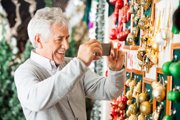 Man Photographing Christmas Ornaments