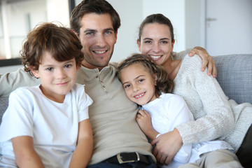 Wall Mural - Happy family of four relaxing in sofa
