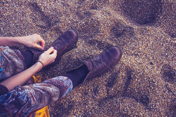 Woman tying her boot laces on the beach