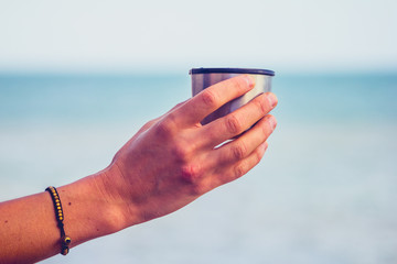 Woman's hand holding a thermos cup by the sea