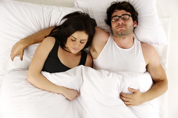 Man and woman laid in white bed asleep cuddling