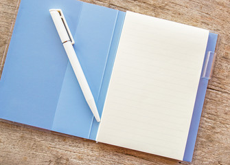 An open notebook and white pen on wood background