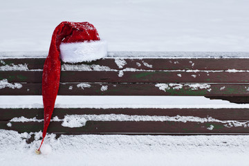 red Santa Claus hat on snow covered bench outdoors