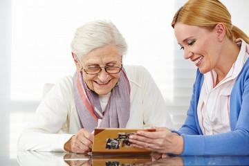 Seniorin schaut mit Tochter Fotoalbum an