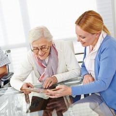 Frau schaut mit Seniorin Fotoalbum an