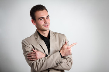 Handsome young man pointing at copyspace with his hand, portrait