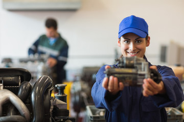 Cheerful trainee presenting part of a machine