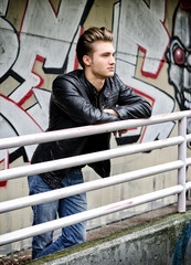 Handsome blond haired young man on metal railing