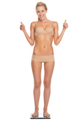 Happy young woman in lingerie standing on scales