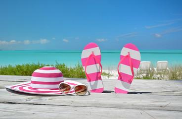 Hat, sunglasses and flip-flops against ocean. Exuma, Bahamas