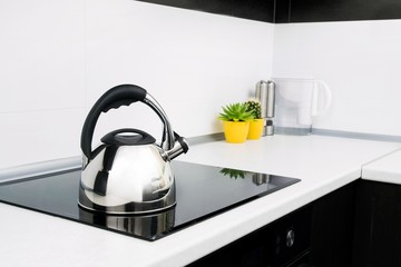 Steel kettle in modern kitchen with induction stove