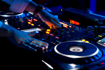 Hands of a DJ mixing music at a disco