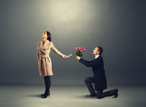 woman don't looking at man with flowers