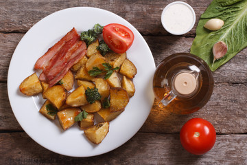 Sliced fried potatoes with bacon and ingredients top view