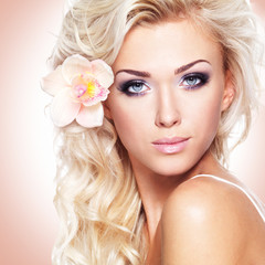 Wall Mural - face of a beautiful woman with white flower in hairs