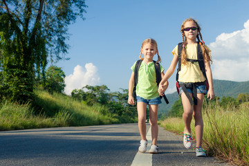 two girls with backpacks walking on the road