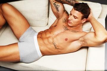 Man with beautiful muscular torso in underwear lying on sofa
