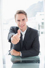 Smiling businessman gesturing thumbs up at office desk