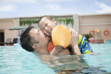 Portrait of father embracing his smiling son in the pool