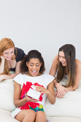 Cheerful young women surprising friend with a gift