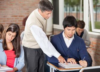Professor Explaining Test To Student In Classroom