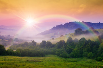 cold fog on hot sunrise in mountains. beautiful summer scenery with rainbow