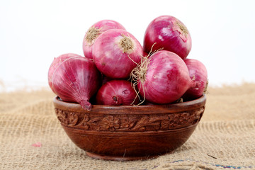 Red onions in a wooden bowl against white