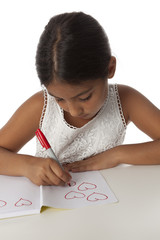 Young teenage girl drawing little hearts