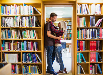 Romantic couple embracing by bookshelves in library